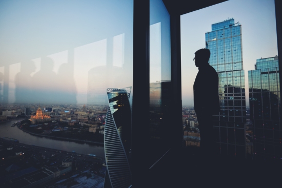 A man in a commercial tower looking over the horizon at dawn.